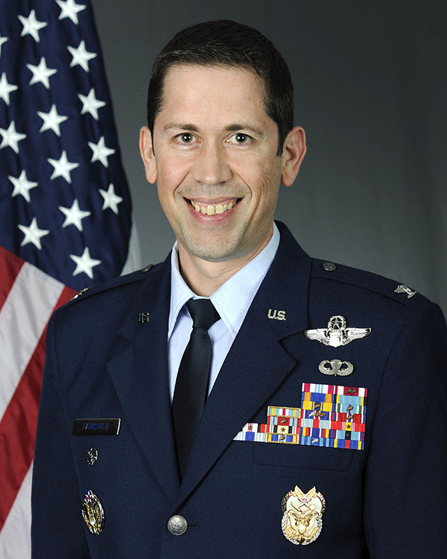White male in Air Force Blues in front of American flag.
