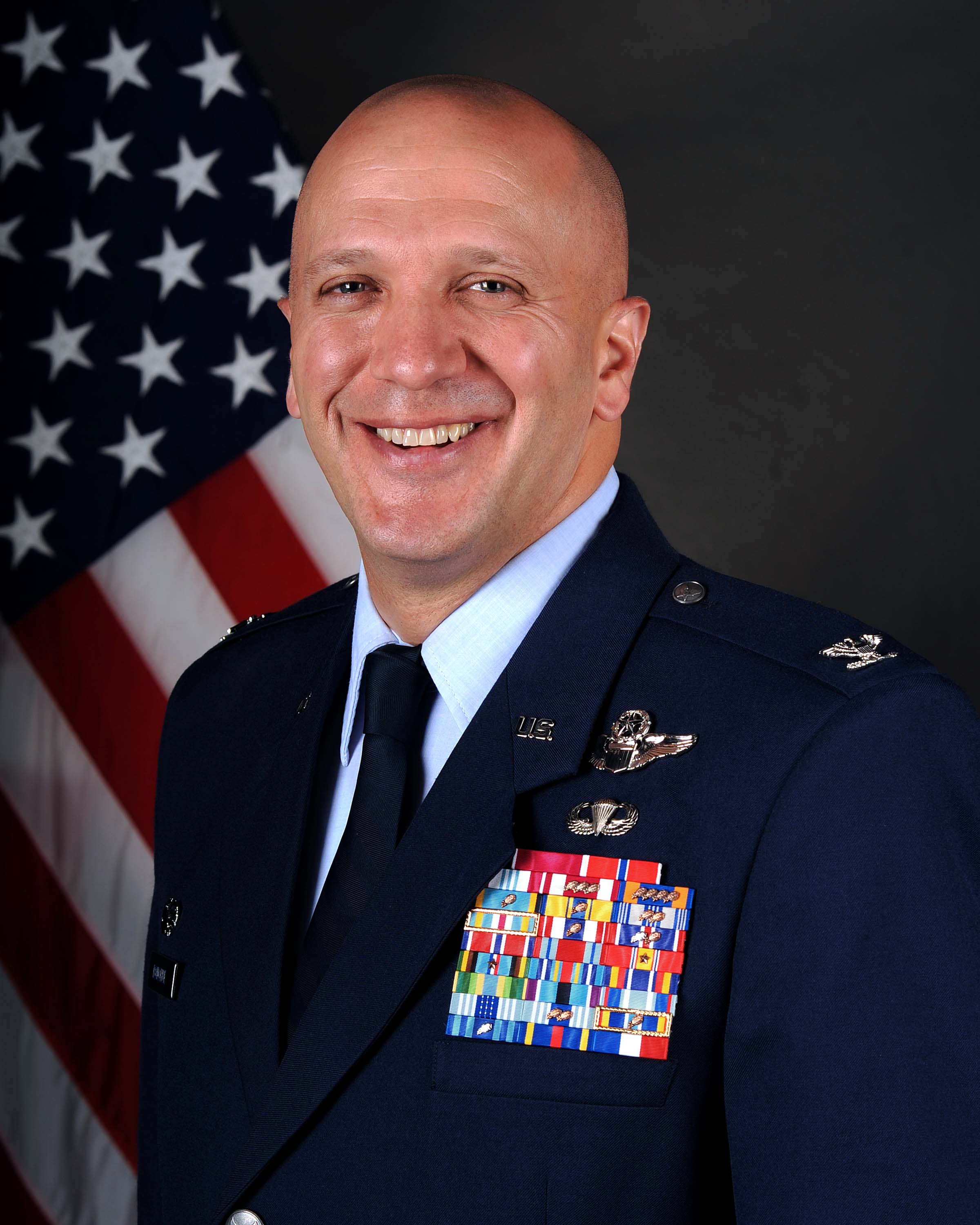 Bald white man in Blue Air Force Uniform in front of Red, white and Blue American flag.