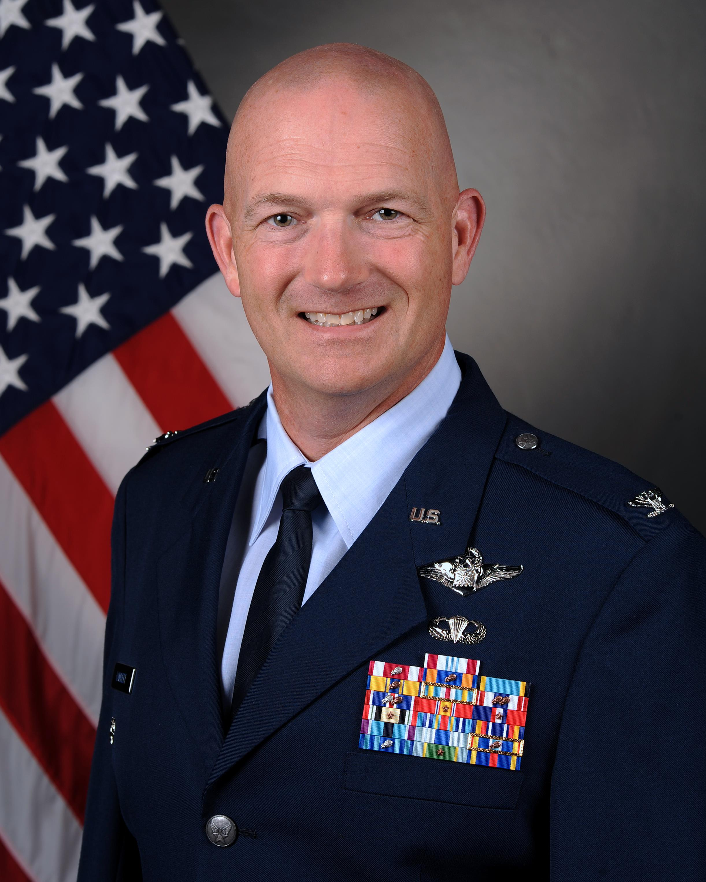 Bald white man in Air Force Blues standing in front of Red, White and Blue American Flag