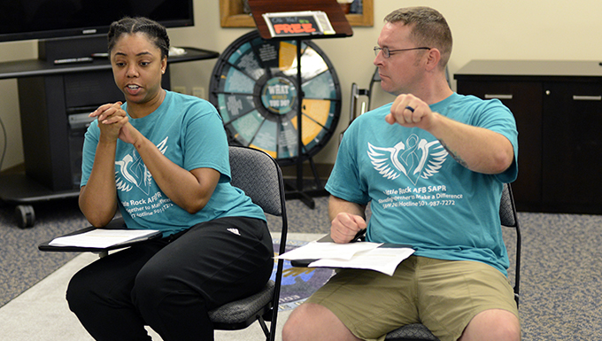 A black female sits next to a white male as they rehearse a Sexual Assault Prevention skit.