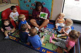 Cheryl Townsend, room lead teacher, reads a book to kids July 10, at Little Rock Air Force Base, Ark. The teachers in the one to two year olds teach kids how to sit quietly and participate during story time.